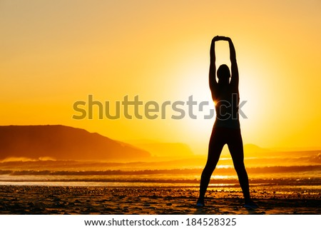 Fitness woman exercising and stretching arms on beautiful summer sunset or morning at beach. Female doing relaxing yoga and breathing exercises. - stock photo