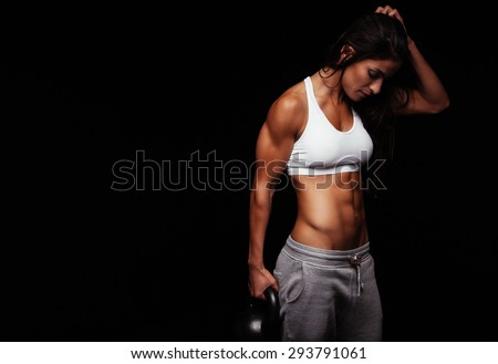 Fitness woman exercising crossfit holding kettle bell. Fitness instructor on black background. Female model with muscular fit and slim body. - stock photo