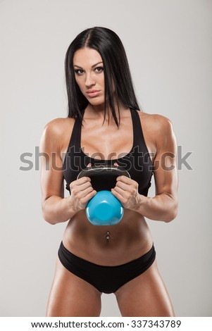 Fitness woman exercising crossfit holding kettlebell strength training biceps. Beautiful fitness instructor on grey background looking intense at camera. Caucasian female mode. - stock photo