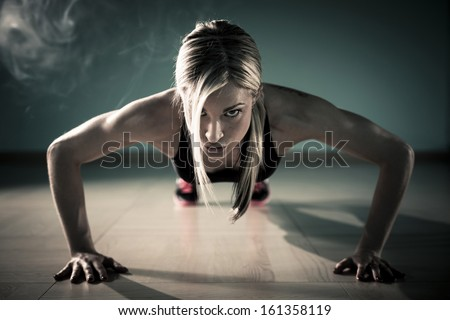 Fitness woman exercising push ups - stock photo