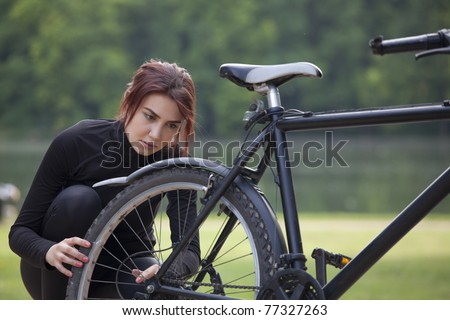 fitness woman has a trouble with mountain bike outdoors - stock photo