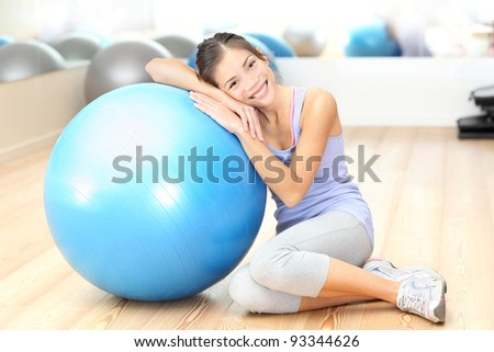Fitness woman in gym resting on pilates ball / exercise ball after training. Beautiful multiracial fitness model in gym. - stock photo