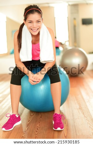 Fitness woman in gym resting on pilates ball / exercise ball relaxing after training. - stock photo