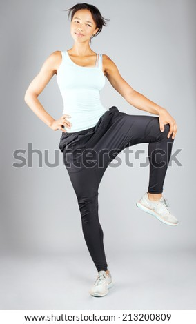 Fitness woman in sport style posing with beautiful smile in studio, looking at camera. - stock photo
