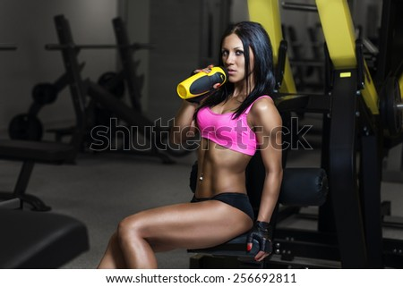fitness woman in sport wear with perfect sexy fitness body in gym drinking from shaker bottle after training - stock photo