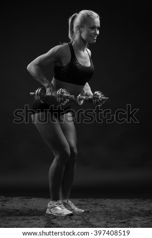 fitness woman in sportswear doing exercises with dumbells. - stock photo