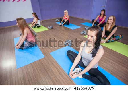 Fitness woman in the group. Gym class. Stretching the legs, twine