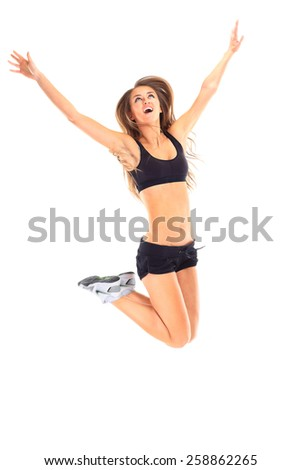 Fitness woman jumping excited isolated on white background. Full body image of beautiful multiracial Asian Caucasian female model in jump flexing.