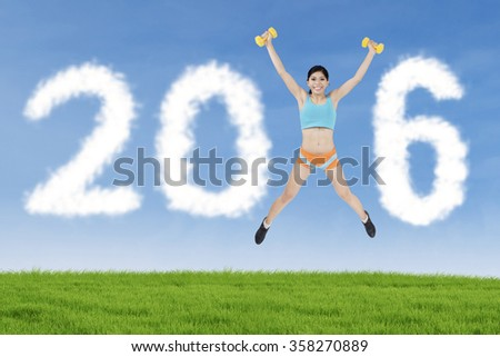 Fitness woman jumping on the meadow with two dumbbells and forming number 2016