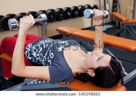 Fitness woman lifting dumbbells and lying in a close up shot