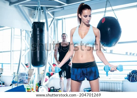 Fitness woman lifting dumbbells. Young couple athletes men and athletes engaged in training with dumbbells and heavy weights. - stock photo