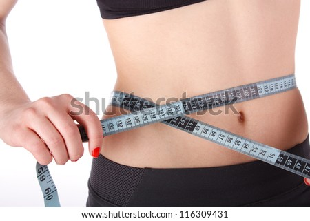 Fitness woman measuring her waist isolated on the white background. - stock photo