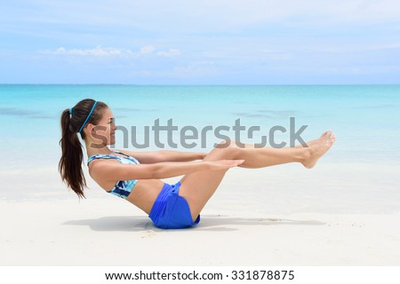 Fitness woman on beach with toned in shape body body doing v-up crunch ab toning exercise workout as part of an active lifestyle for weight loss. - stock photo