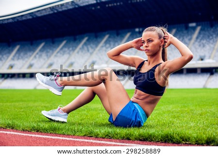 Fitness woman on stadium doing abdominal exercise  - stock photo