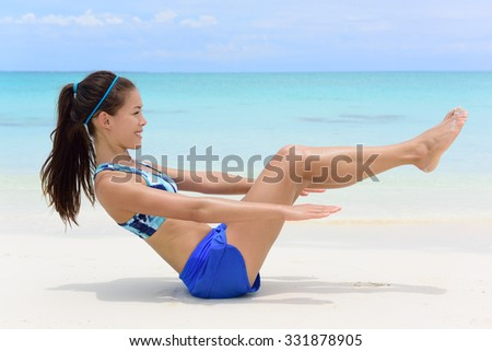 Fitness woman on white sand beach and turquoise ocean background exercising abs with sit-ups workout. Young female athlete doing ab toning exercises with v-up crunches as basic core body poses. - stock photo