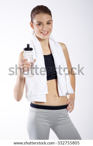 Fitness woman portrait with a towel and bottle isolated on white background - stock photo