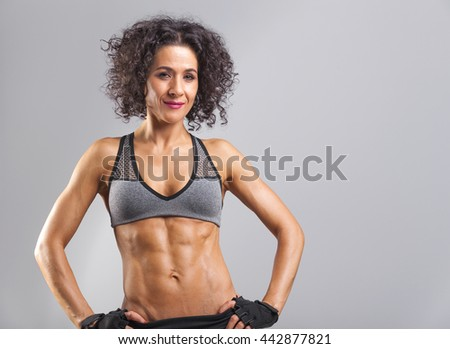 Fitness woman posing on gray background - stock photo
