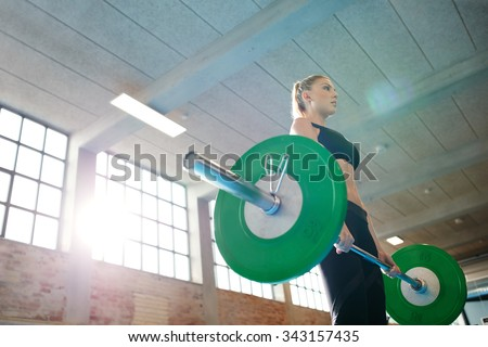 Fitness woman preparing to practice deadlift with heavy weights in gym. Female doing heavy weight lifting work out in health club. - stock photo