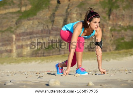 Fitness woman ready for running on beach. Female runner with earphones and arm sport band in starting line pose. - stock photo