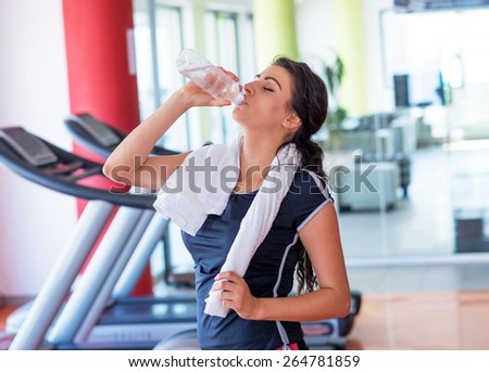 Fitness woman relax with water bottle after exercise at the gym - stock photo