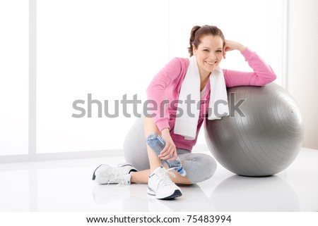 Fitness woman relax with water bottle exercise ball