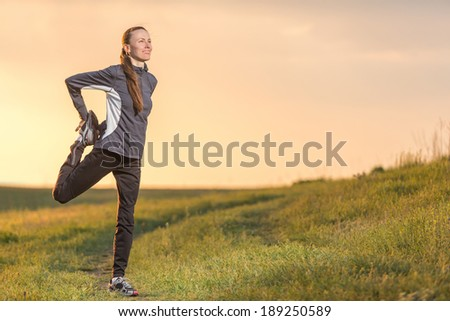 Fitness woman runner relaxing after outdoor running and working out. An attractive female runner stretching before workout