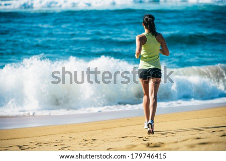 Fitness woman running towards the sea on beach. back view runner. - stock photo