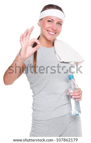 fitness woman showing ok sign and smiling. studio shot over white background
