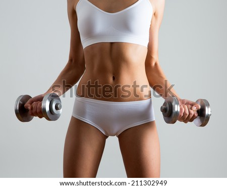 Fitness woman. Slim woman with dumbbells. - stock photo