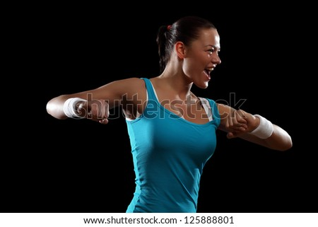 Fitness woman smiling standing against black background