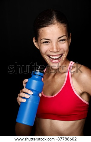 Fitness woman smiling with happy fresh energy while sweating and drinking water from bottle. Chinese Asian / white Caucasian female model on black background. - stock photo