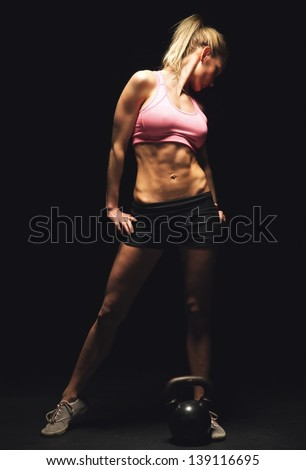 Fitness woman standing and showing off her toned and muscular athletic body - stock photo