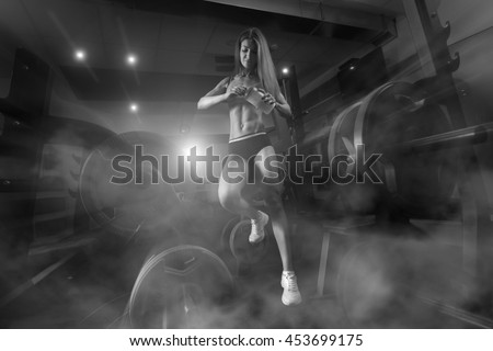 Fitness woman standing in a smoky gym. Fitness woman in the gym. Fitness girl with shaker posing in the gym. Fitness - concept of healthy lifestyle. Perfect fitness body.