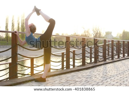 Fitness woman stretching and workout pose next to a lake during sunset. Young woman warming up.