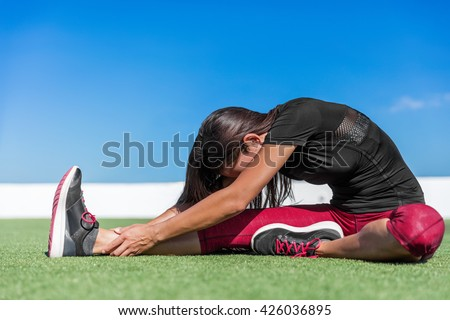 Fitness woman stretching back and leg muscles with toe-touch stretches. Sporty young athlete doing a one leg seated forward bend yoga stretch on outdoor grass. Sitting head to knee fold over pose. - stock photo