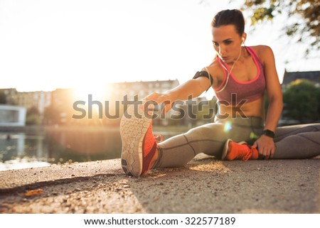 Fitness woman stretching before a run. Young female runner stretching her muscles before a training session. She is sitting on sidewalk along a pond in city on a sunny day with sun flare. - stock photo