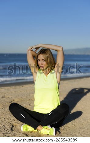 Fitness woman stretching her arms outdoors near the beach