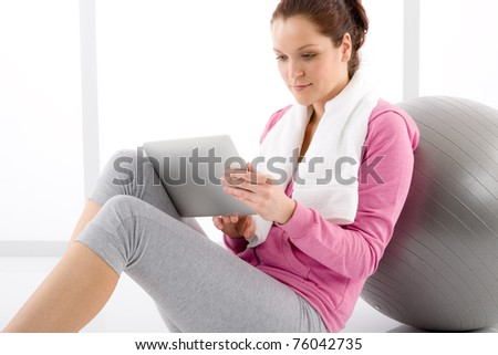 Fitness woman touch screen computer sportive outfit gym - stock photo