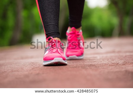 Fitness woman training and jogging in summer park, close up on running shoes
