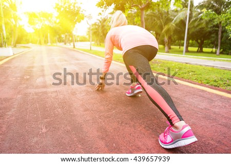 Fitness woman training and jogging in summer park, ready to start. Healthy lifestyle and sport concept