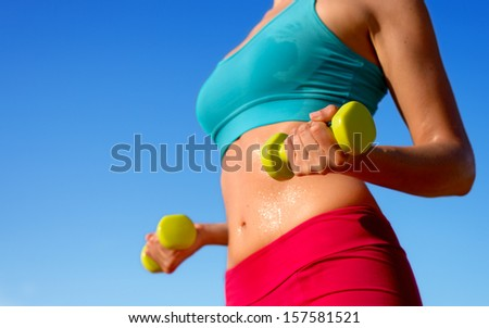 Fitness woman training hard with dumbbells and sweating in summer. Fit sporty girl exercising biceps and arms with weights on blue sky background. - stock photo