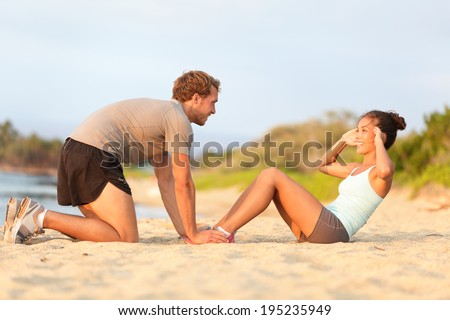 Fitness woman training situp crunches with personal trainer instructor. Young couple happy working out in sand on beach. Beautiful Asian female model and male fitness model holding her feet exercising - stock photo
