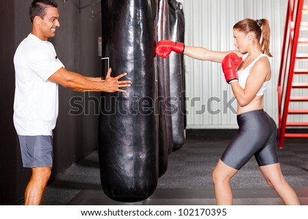 fitness woman training with punch bag in gym with personal trainer - stock photo
