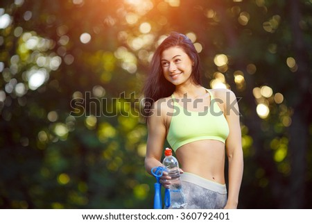 Fitness woman with a skipping rope and a bottle of water outdoors . Fitness training outdoors. Fitness classes outdoors. Attractive fitness woman. Sports and fitness - concept of healthy lifestyle. - stock photo