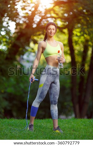 Fitness woman with a skipping rope and a bottle of water outdoors. Fitness training outdoors. Fitness classes outdoors. Attractive fitness woman. Workout outdoors. Healthy lifestyle  - stock photo