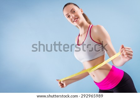 Fitness Woman With Tape Measure On Blue Background - stock photo