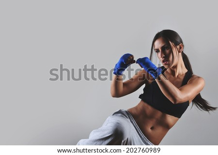 fitness woman with the blue boxing bandages, studio shot - stock photo