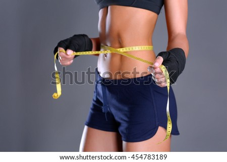 Fitness womans beautiful body with measure tape - stock photo