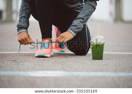 Fitness workout and healthy nutrition concept.  Detox smoothie drink and running footwear close up. Female athlete tying sport shoes laces before training outdoor. - stock photo