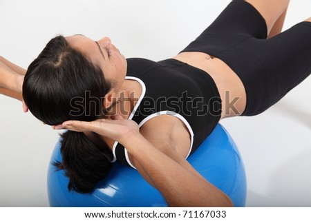 Fitness workout by young woman using exercise ball